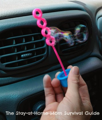 Blow bubbles as a car activity on a road trip with kids.