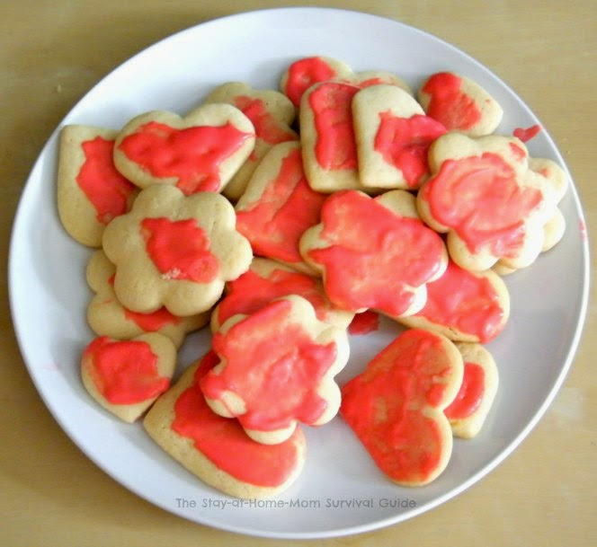 Bake sugar cookies shaped like hearts and flowers to place in homemade Valentine treat bags-simple idea for even the not-so-crafty moms! Idea and recipe shared at The Stay-at-Home-Mom Survival Guide.