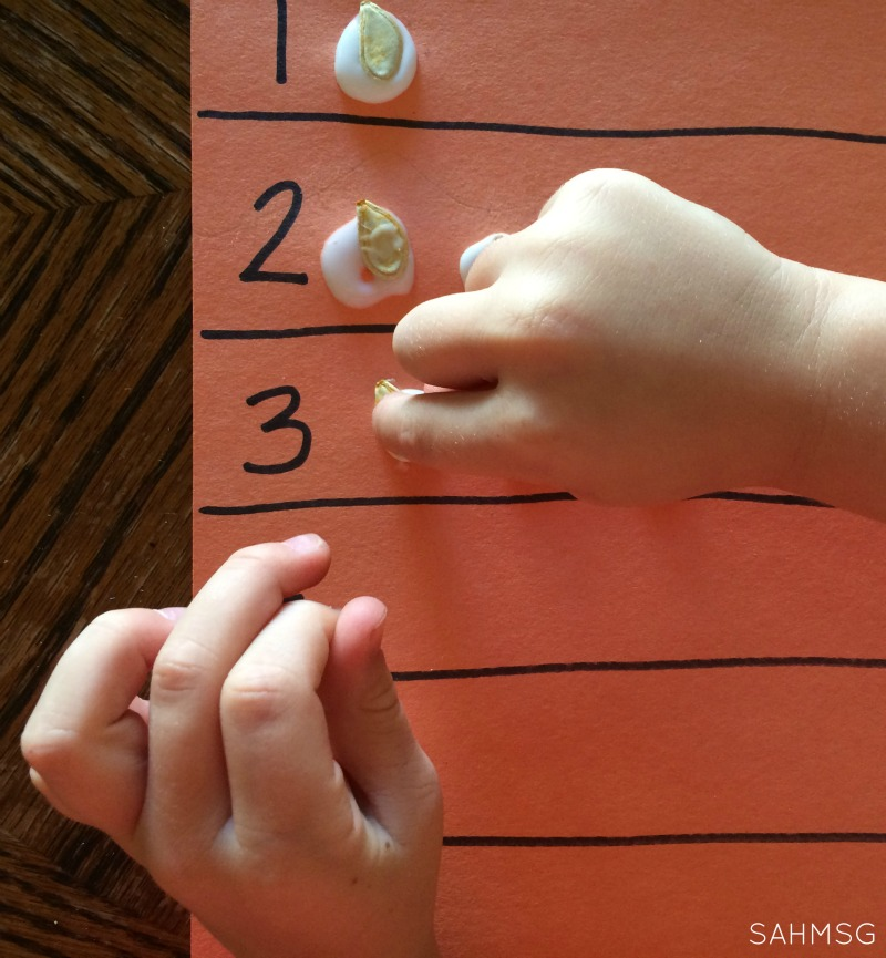 Fine motor work gluing pumpkin seeds for counting and number recognition practice for preschool. Pumpkin or Fall theme activity.