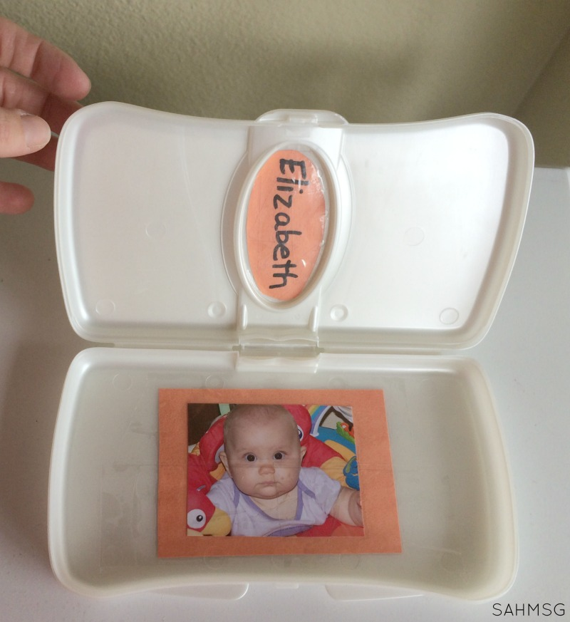 DIY Toy for Babies: Personalized Peek-A-Boo Box out of a travel wipes container.